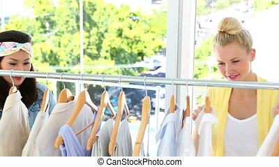 Pretty friends looking through clothing rail together in...