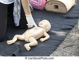 First aid - Paramedic demonstrates CPR on infant dummy