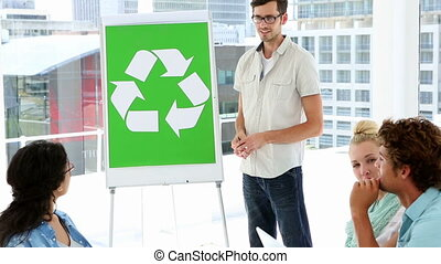 Man present environmental awareness plan to coworkers in a...