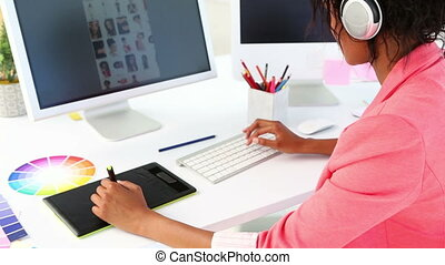 Pretty photo editor working with digitizer at her desk in...