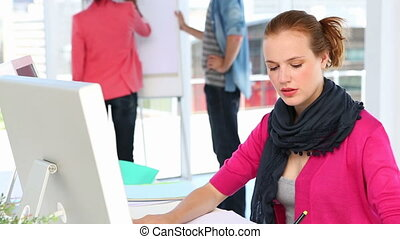 Pretty designer working with graphics tablet at her desk in...
