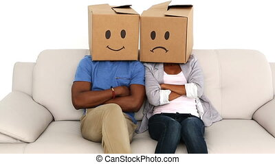 Team sitting on sofa with emoticon boxes on their heads in...