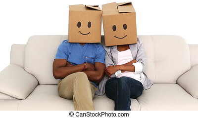 Team sitting on couch with emoticon boxes on their heads in...