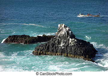 Craggy coastline - Fishing boat along craggy coastline in...