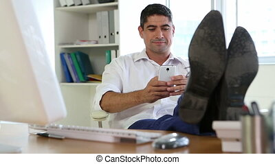 Businessman answering the phone with feet up on desk in his...