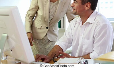 Business team working together on computer and smiling in...