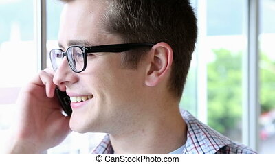 Casual businessman smiling and speaking on phone in the...