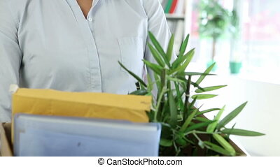 Fired businesswoman holding box of her things in the office