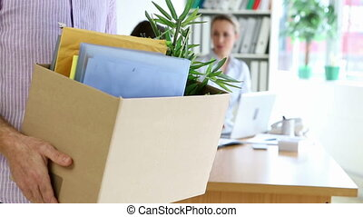 Fired businessman holding box of his things in the office