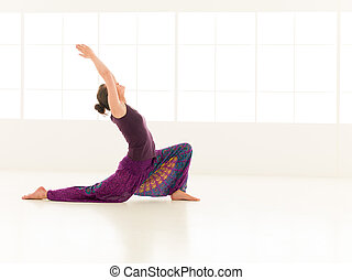 Anjaneyasana yoga pose - side view of woman sitting in yoga...