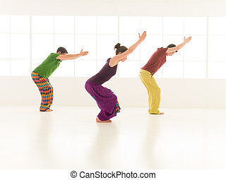 yoga posture Utkatasana - Three students performing...