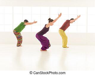 yoga posture Utkatasana - Three students performing...