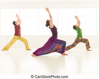 group yoga virabhadrasana - Three young people one omen and...