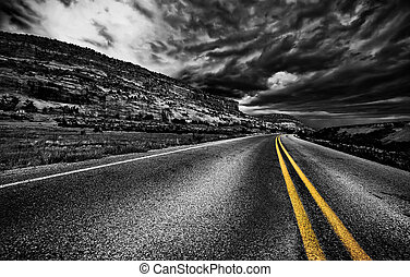 Rural road, USA - Road in the field with dramatic gray sky,...