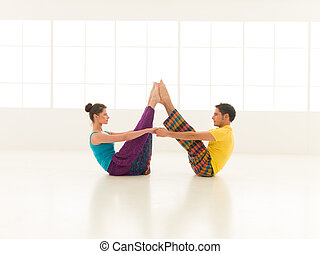 yoga partners - beautiful woman with a handsome man dressed...