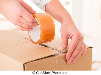 Transparent tape - Hands with roll of transparent packaging,...