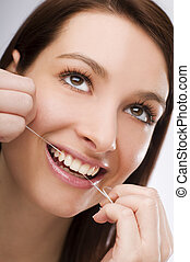 floss - young Woman flossing teeth close up shoot