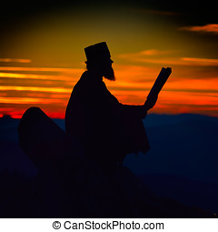 silhouette of priest reading in the sunset light