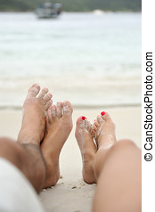 couples feet on perfect tropical beach resting - Feet of a...