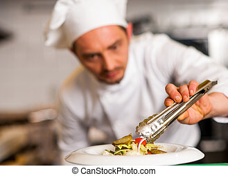 Chef arranging tossed salad in a white bowl - Image of a...