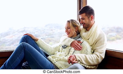 Cute couple relaxing together in their winter cabin on a...