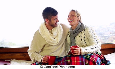 Cute couple relaxing together under a blanket in their...