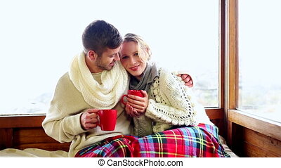 Cute couple relaxing together under a blanket in their ski...
