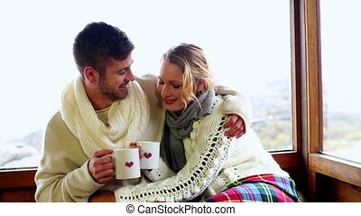 Cute couple cuddling together under a blanket in their ski...