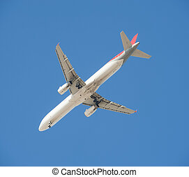 Large passenger aircraft in flight against blue sky - Large...