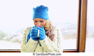 Cute blonde drinking from mug in a ski lodge wearing winter...