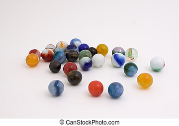 Marbles spread on whte - a group of marbles on a white...