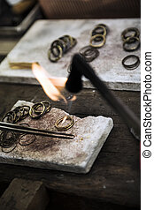 Jewelery making - Jeweler crafting golden rings with flame...
