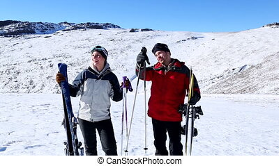 Active couple holding skis and poles pointing to the ski...