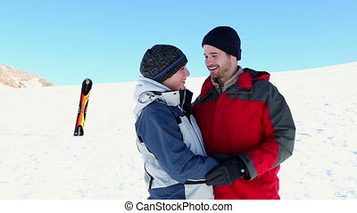 Happy couple standing outside in the snow on a ski holiday