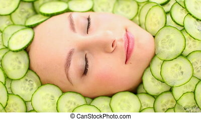 Natural womans face surrounded by cucumbers