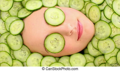 Smiling womans face surrounded by cucumbers