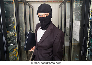 robber in black mask hack server room downloading data on...