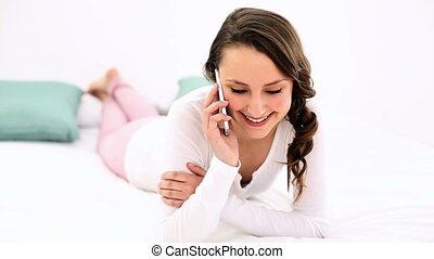 Smiling woman lying on bed chatting