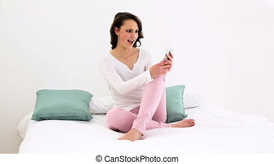 Smiling woman sitting on bed texting on the phone at home in...