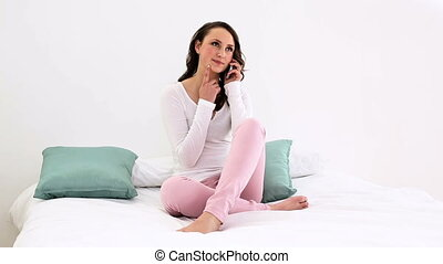 Smiling woman sitting on bed talking
