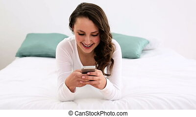 Smiling woman lying on bed texting on her phone at home in...