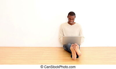 Smiling man using laptop sitting on the floor in an empty...