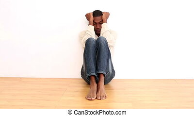 Anxious man sitting on the floor in an empty room