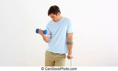Injured man lifting dumbbell on white background