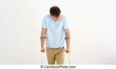 Injured man on crutches stepping towards camera on white...