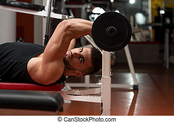 Man In The Gym Exercising Triceps With Barbell - Muscular...