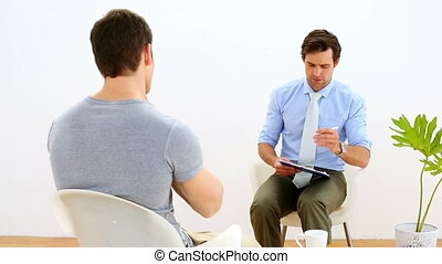 Physiotherapist speaking with patient with neck pain in his...
