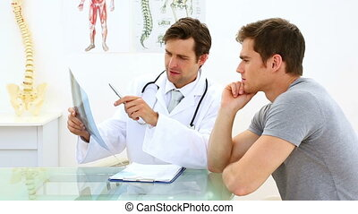 Handsome doctor discussing xray with his patient in his...
