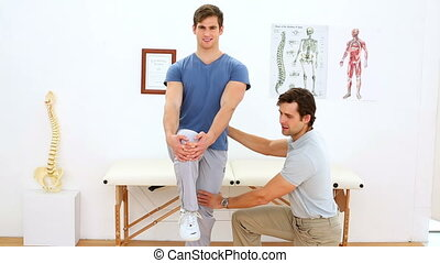 Physiotherapist checking knee of injured patient in an...