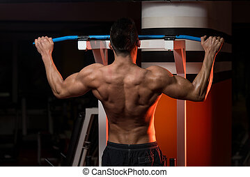Muscular Young Man Exercising In Gym - Young Male...